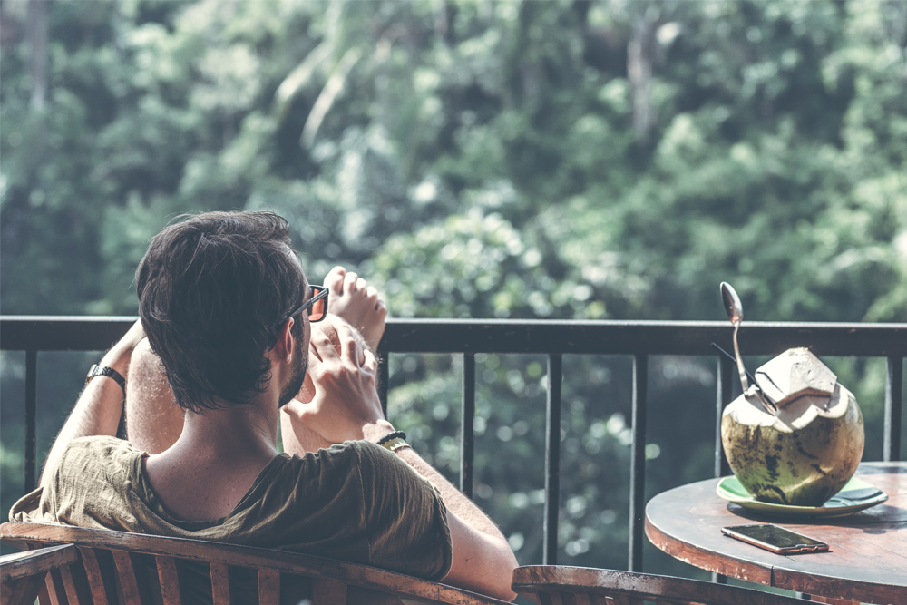 shot of man relaxing on balcony drinking from coconut