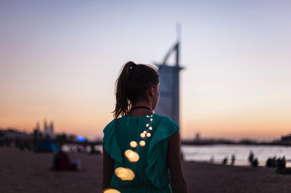 girl standing on beach near burj al arab