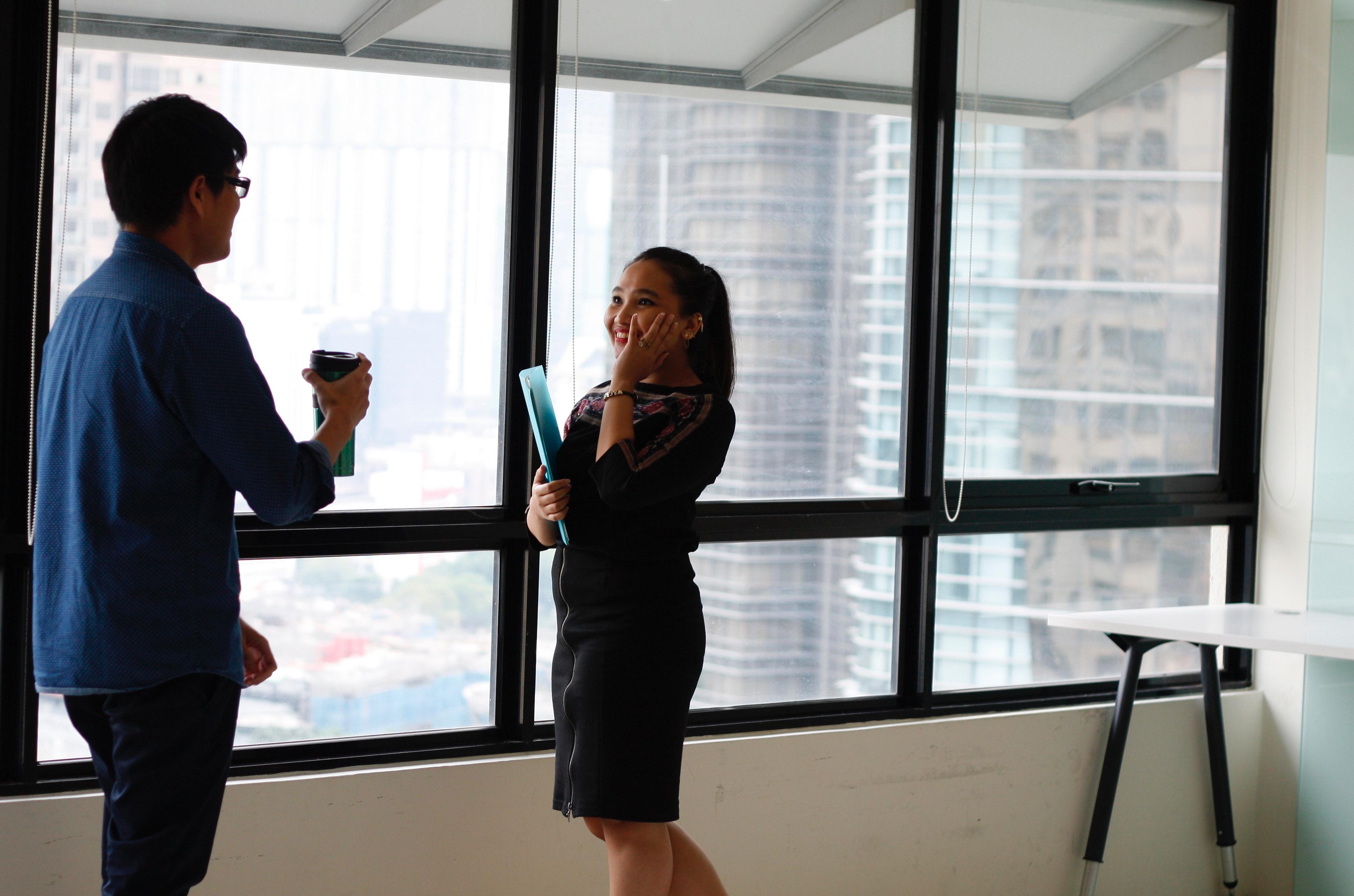 man woman talking in office near window