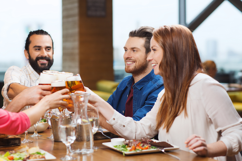 friends sitting at table cheering with beer glasses
