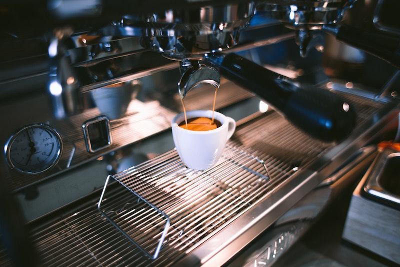 white cup of espresso in coffee machine