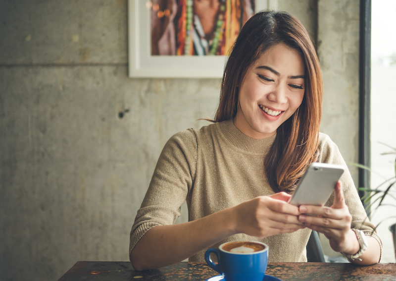 woman smiling using mobile phone at table in cafe
